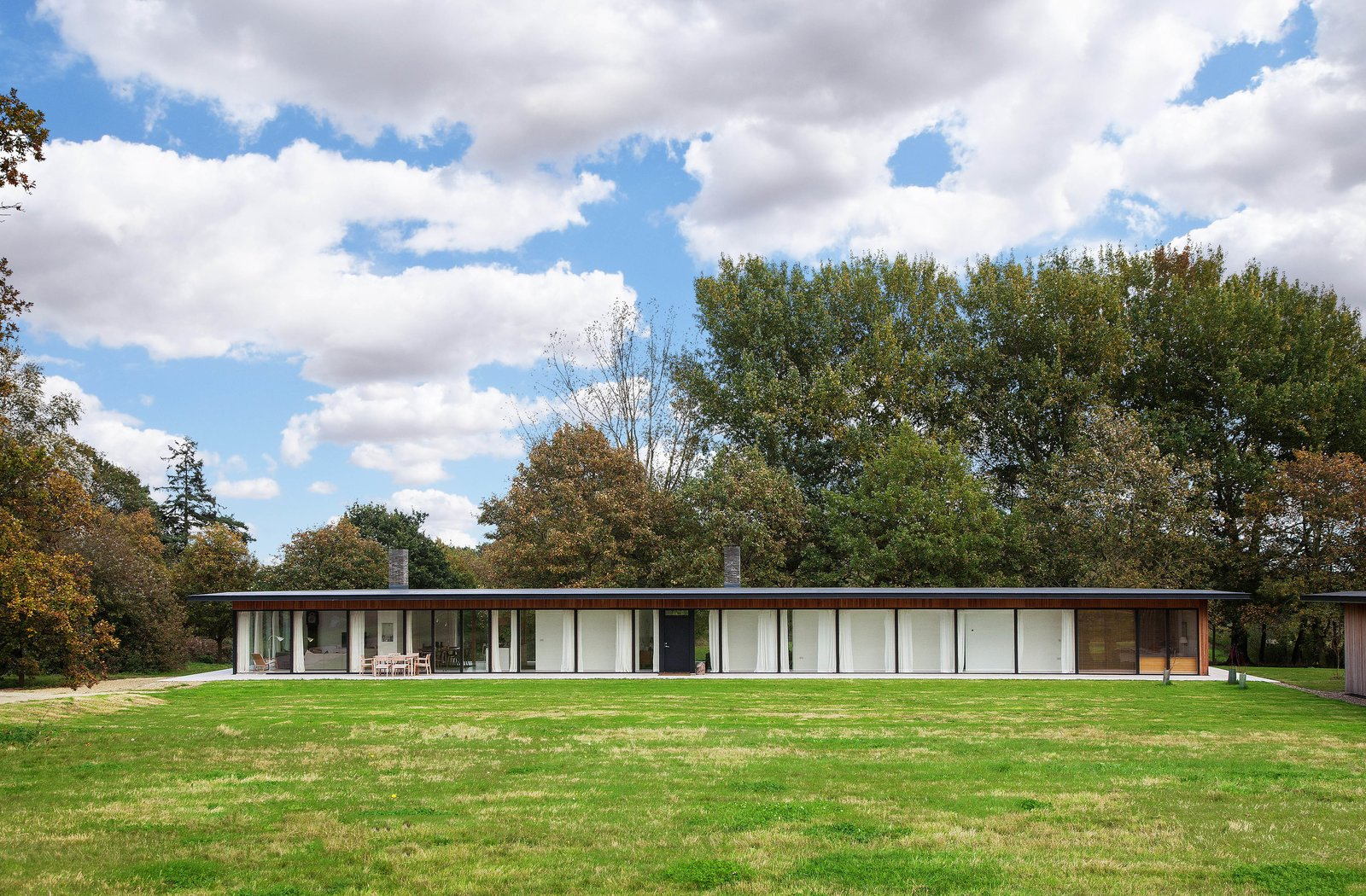 Outdoor, Large Patio, Porch, Deck, Back Yard, Grass, and Trees The steel frame and low profile with expanses of glass calls to mind the style of Mies van der Rohe.  Photo 11 of 11 in A Scandinavian-Style Pavilion in England Is Listed For $2.1M