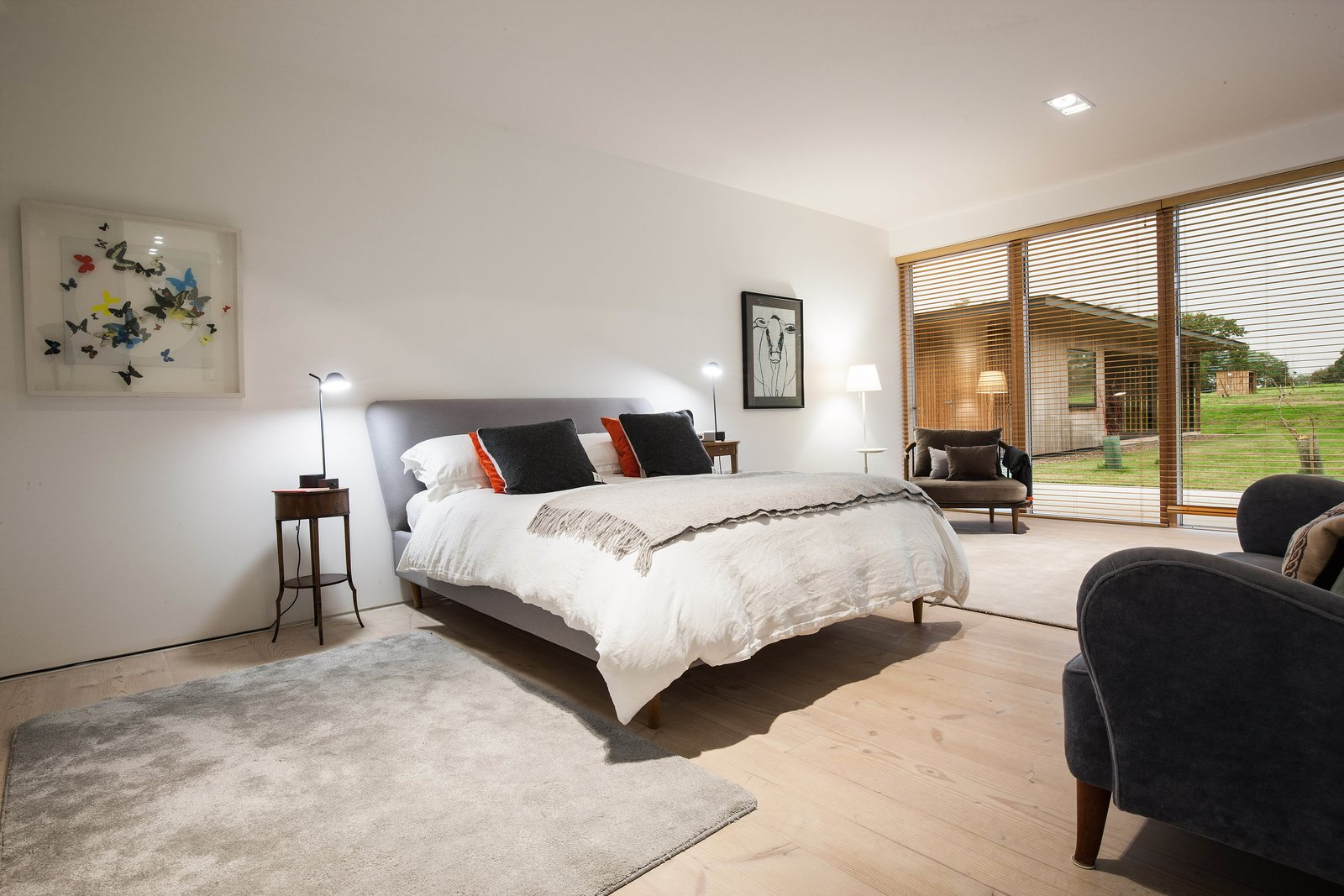 Bedroom, Chair, Night Stands, Light Hardwood, Bed, Table, Recessed, Rug, and Lamps The master bedroom offers a view of the exterior annex.  Best Bedroom Recessed Lamps Photos from A Scandinavian-Style Pavilion in England Is Listed For $2.1M