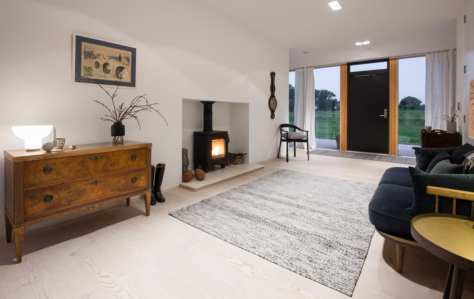 Living Room, Wood Burning Fireplace, Light Hardwood Floor, Rug Floor, Storage, End Tables, Sofa, Chair, Table Lighting, and Recessed Lighting A sitting area with a stove creates a cozy sense of  Photo 4 of 11 in A Scandinavian-Style Pavilion in England Is Listed For $2.1M