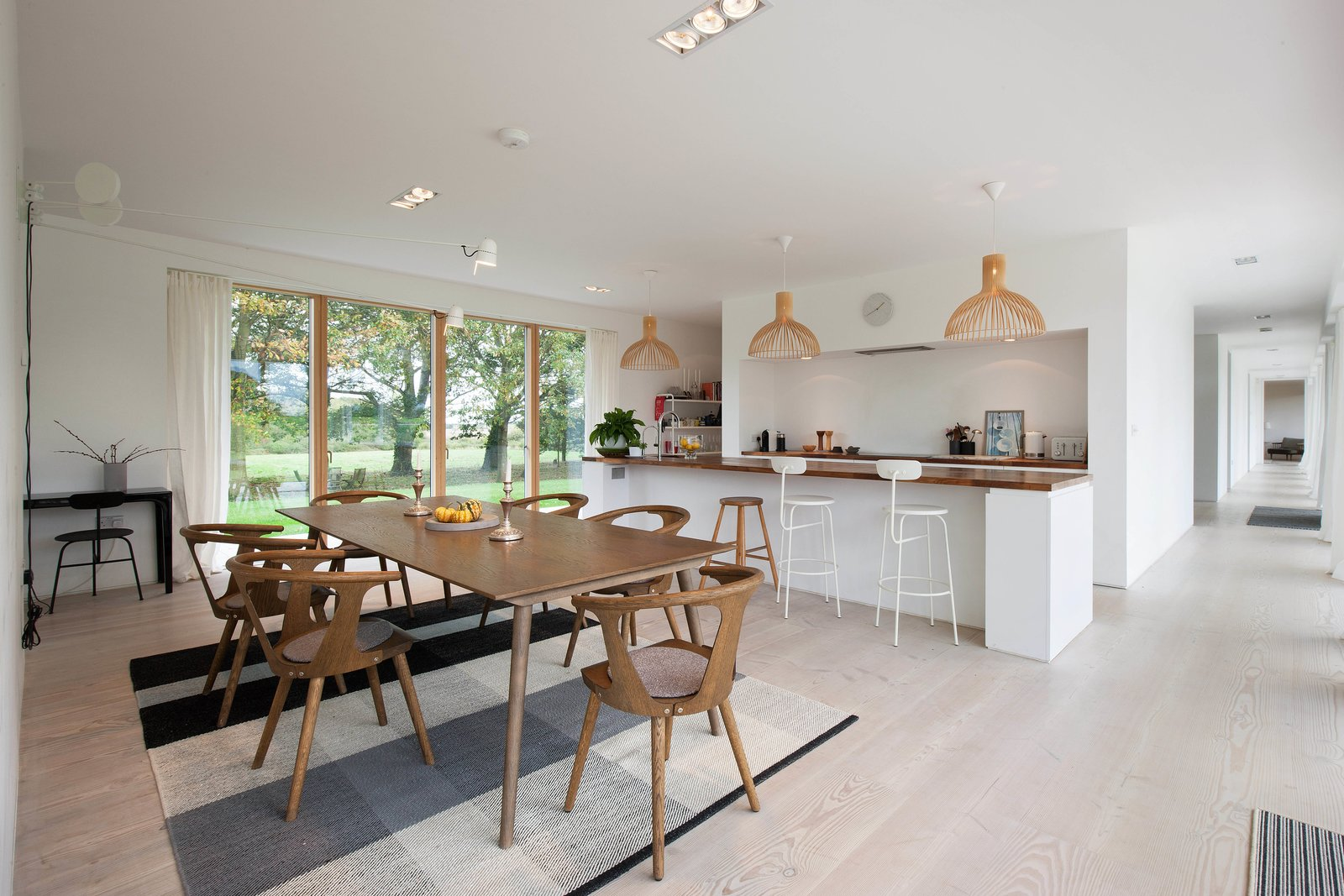 Dining Room, Stools, Recessed Lighting, Table, Light Hardwood Floor, Chair, Bar, Wall Lighting, and Pendant Lighting The bright, open, contemporary kitchen.  Photo 1 of 11 in A Scandinavian-Style Pavilion in England Is Listed For $2.1M