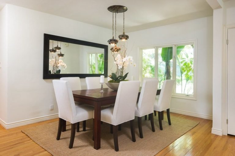 Dining Room, Pendant Lighting, Medium Hardwood Floor, Rug Floor, Chair, and Table The dining room nook is set off the living area.  Photo 10 of 16 in Anna Faris Lists Her Midcentury Abode in the Hollywood Hills For $2.5M