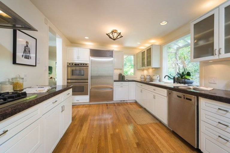 Kitchen, Wall Oven, White Cabinet, Medium Hardwood Floor, Dishwasher, Refrigerator, Range Hood, Ceiling Lighting, Recessed Lighting, and Range The kitchen is both functional and beautifully designed.  Photo 11 of 16 in Anna Faris Lists Her Midcentury Abode in the Hollywood Hills For $2.5M
