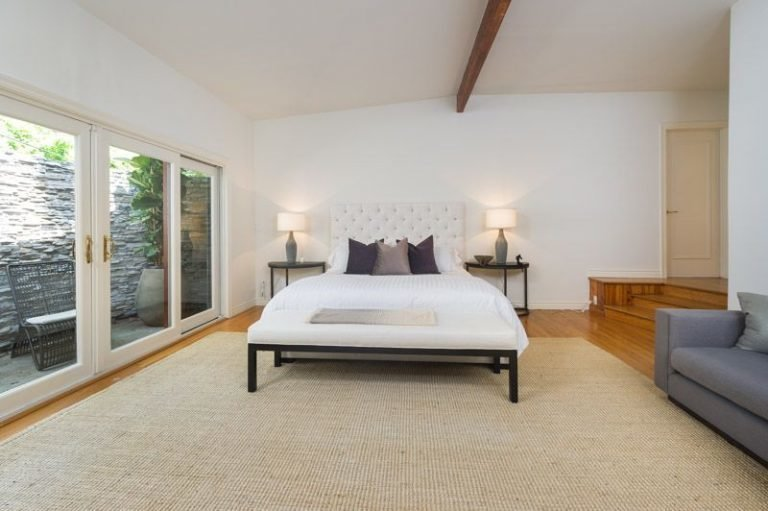 Bedroom, Table Lighting, Bed, Night Stands, Medium Hardwood Floor, and Rug Floor The master suite is like an oasis.  Photo 12 of 16 in Anna Faris Lists Her Midcentury Abode in the Hollywood Hills For $2.5M