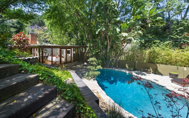 Outdoor, Back Yard, Trees, Shrubs, Garden, Walkways, Small Patio, Porch, Deck, Large Pools, Tubs, Shower, and Swimming Pools, Tubs, Shower The lagoon-like po  Photo 2 of 16 in Anna Faris Lists Her Midcentury Abode in the Hollywood Hills For $2.5M