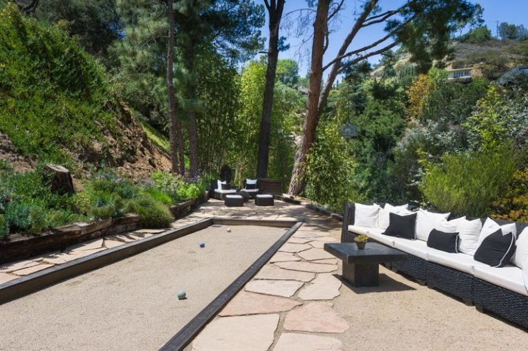 Outdoor, Stone Patio, Porch, Deck, Garden, Trees, Back Yard, Walkways, Hardscapes, Shrubs, and Large Patio, Porch, Deck A bocce court is  Photo 3 of 16 in Anna Faris Lists Her Midcentury Abode in the Hollywood Hills For $2.5M