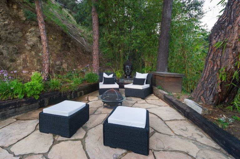 Outdoor, Hardscapes, Large Patio, Porch, Deck, Stone Patio, Porch, Deck, Shrubs, Garden, Back Yard, Trees, and Walkways A backyard fire pit for cool California evenings.  Photo 5 of 16 in Anna Faris Lists Her Midcentury Abode in the Hollywood Hills For $2.5M