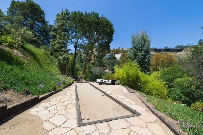 Outdoor, Back Yard, Trees, Garden, Stone Patio, Porch, Deck, Hardscapes, Walkways, Shrubs, and Large Patio, Porch, Deck Stunning panoramic views.  Photo 4 of 16 in Anna Faris Lists Her Midcentury Abode in the Hollywood Hills For $2.5M