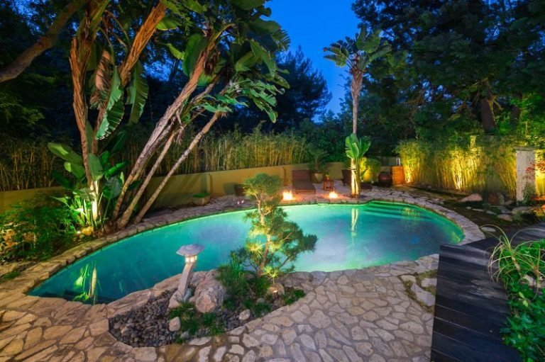 Outdoor, Back Yard, Gardens, Stone Patio, Porch, Deck, Walkways, Large Pools, Tubs, Shower, Swimming Pools, Tubs, Shower, and Trees The lagoon-like swimming pool.  Photo 7 of 16 in Anna Faris Lists Her Midcentury Abode in the Hollywood Hills For $2.5M
