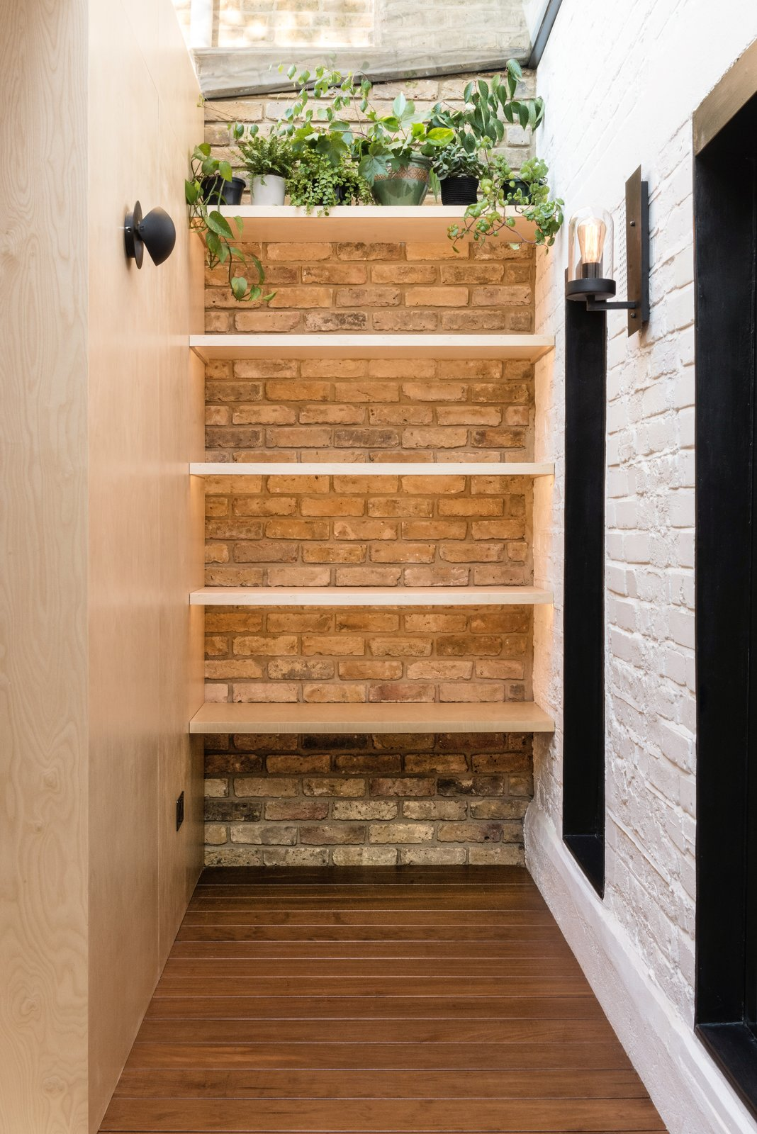 Office, Bookcase, Medium Hardwood Floor, and Study Room Type The walls are made of exposed bricks in reference to the original Victorian house.  Photo 6 of 11 in A Crafty Triangular Addition Carves Out Office Space in a London Backyard