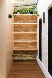 The walls are made of exposed bricks in reference to the original Victorian house.