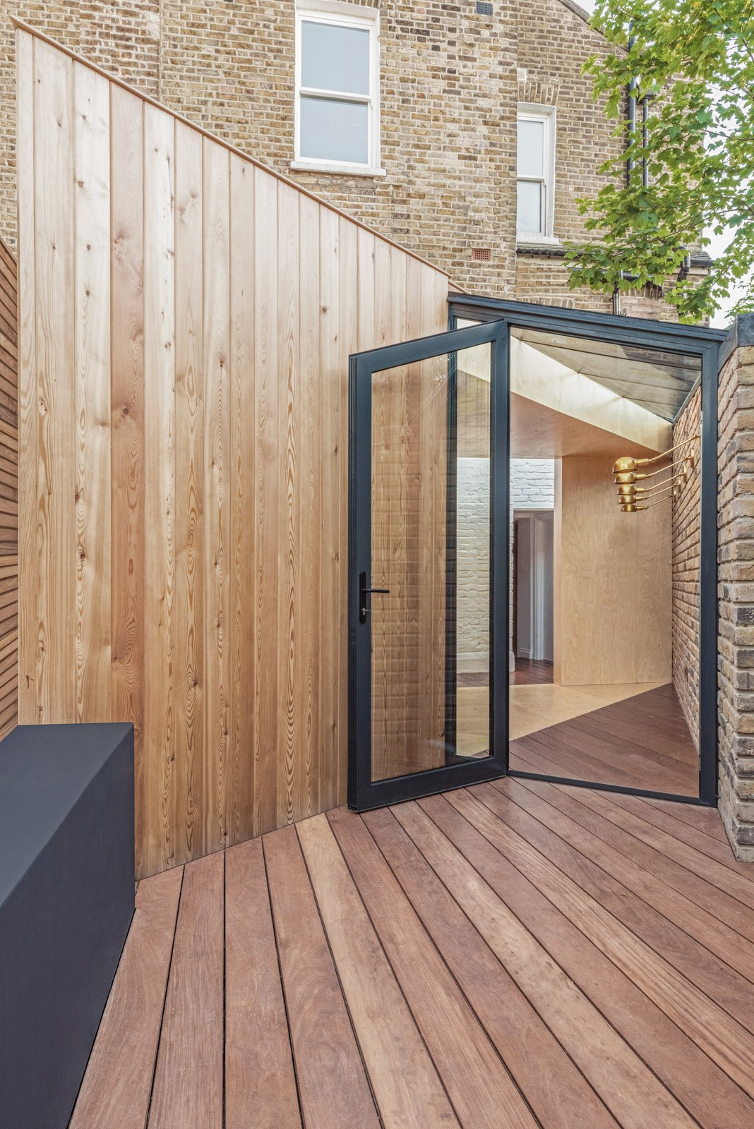 Outdoor, Back Yard, Small Patio, Porch, Deck, and Decking Patio, Porch, Deck The patio area floor is finished with a dark-stained decking, surrounding and contrasting the pale-colored plywood.  Best Photos from A Crafty Triangular Addition Carves Out Office Space in a London Backyard