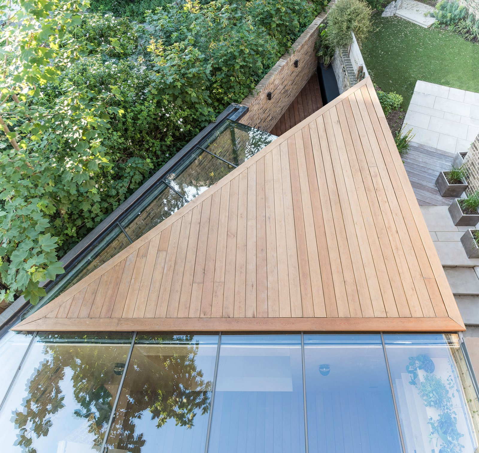 Outdoor, Decking Patio, Porch, Deck, Back Yard, Small Patio, Porch, Deck, Wood Patio, Porch, Deck, Rooftop, and Garden An overhead view of the extension.  Photos from A Crafty Triangular Addition Carves Out Office Space in a London Backyard