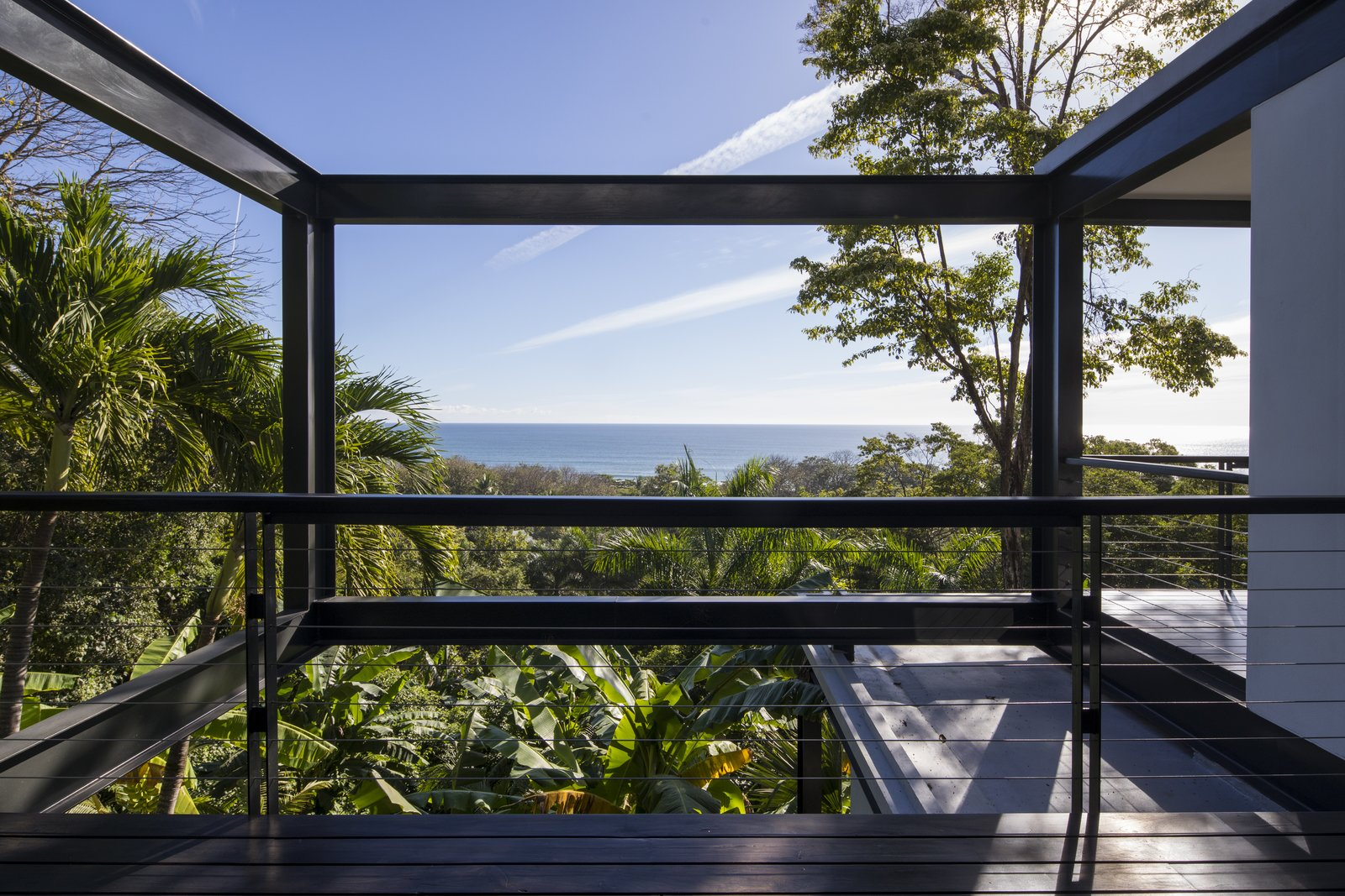 Outdoor, Decking, Trees, Wire, Wood, Metal, and Back Yard The villa's location is just a stone's throw from the sea.  Best Outdoor Decking Metal Photos from Slip Away to These Sleek New Villas in a Costa Rican Forest