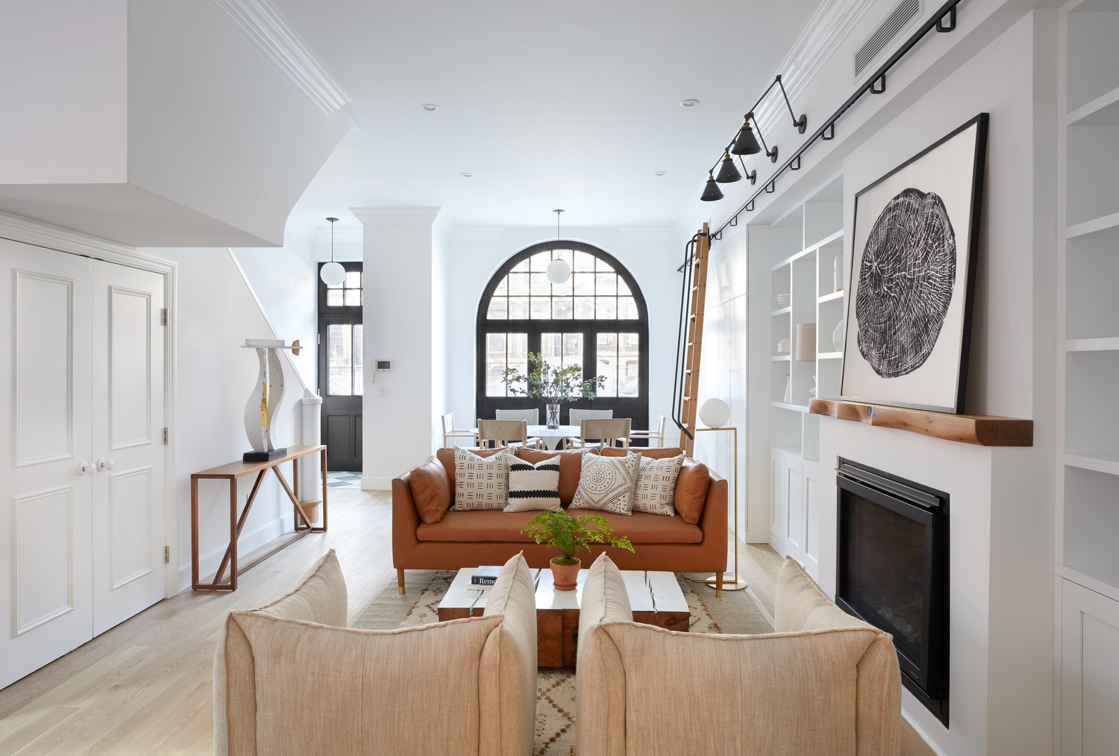 Living, Track, Ceiling, Bookcase, Pendant, Chair, Console Tables, Coffee Tables, Sofa, Gas Burning, Accent, and Light Hardwood Built-in shelving and a gas fireplace with a customized mantel by Fitzhugh Karol preside over 411 Vanderbilt's living room.  Best Living Track Console Tables Photos from Two Renovated Carriage Houses in Brooklyn Hit the Market