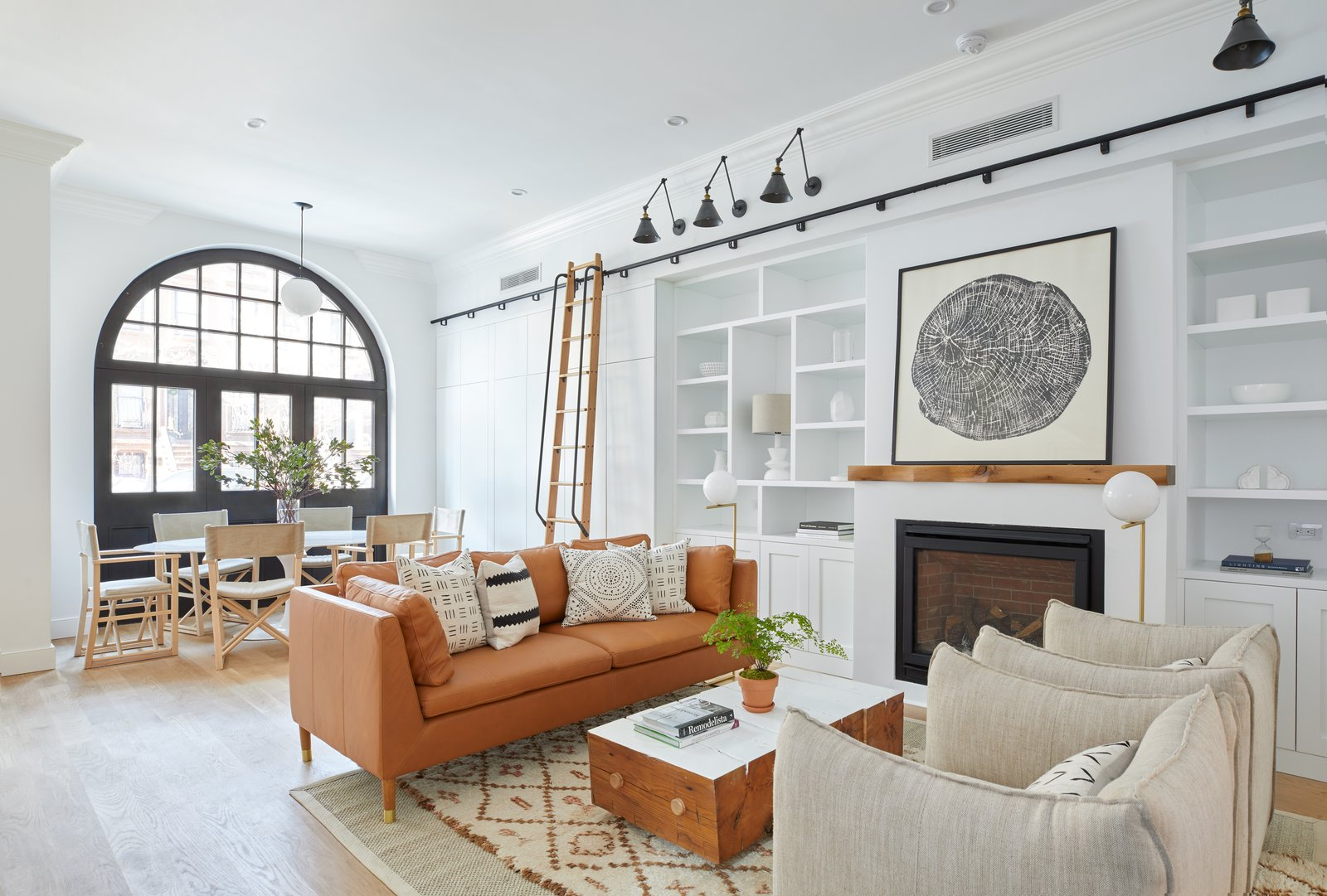 Living, Accent, Track, Light Hardwood, Sofa, Bookcase, Coffee Tables, Chair, Pendant, Gas Burning, and Ceiling The light-filled, lovely living room of 411 Vanderbilt.  Best Living Pendant Gas Burning Photos from Two Renovated Carriage Houses in Brooklyn Hit the Market