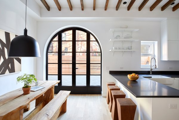 White kitchens with black countertops don't have to give a harsh vibe. This crisp, clean, eat-in kitchen boasts high-end appliances from Viking, Bosch, Sub-Zero, and LG. An arched carriage entrance and exposed beams connect the kitchen to this home's rich past.