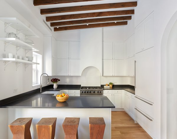 A crisp, clean, eat-in kitchen with high-end appliances from Viking, Bosch, Sub-Zero, and LG make this space a chef's delight, while exposed beams, an arched stove hood, and a second arched carriage entrance along the back wall connect the room to the home's rich past.