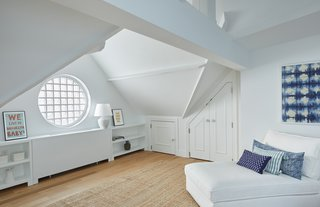 The third floor of 411 Vanderbilt features a fourth private bedroom with peaked ceilings, exposed beams, an en-suite bath and a beautiful round window.