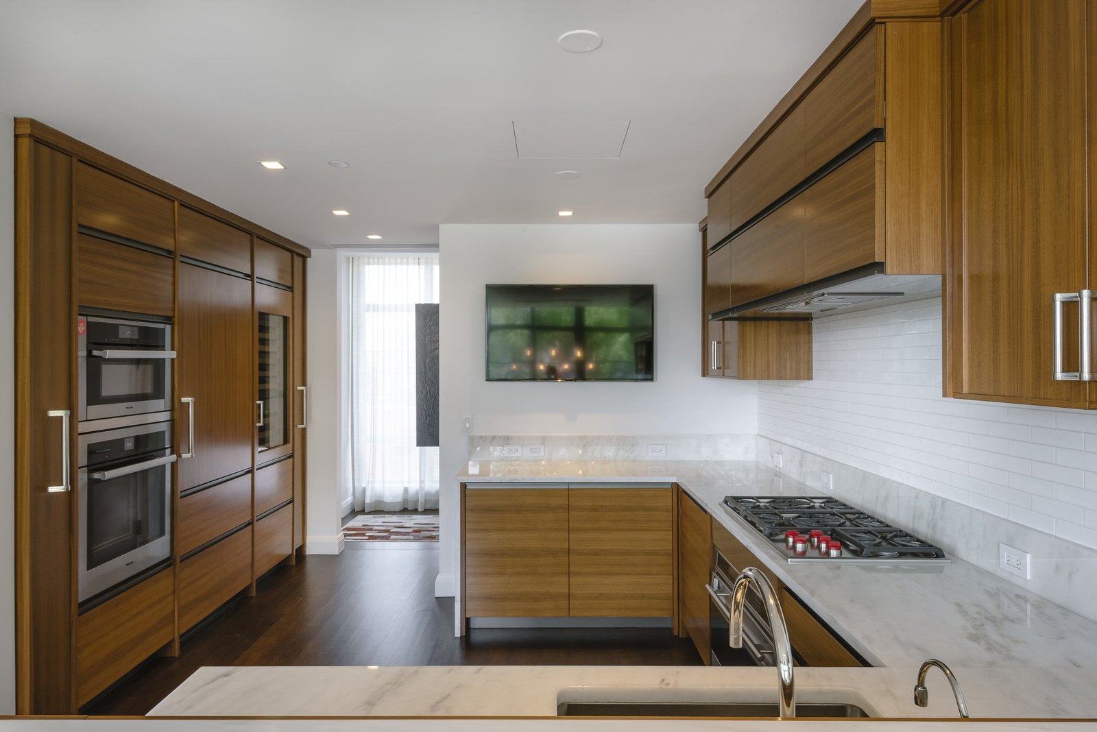 Kitchen, Marble, Range, Wall Oven, Ceiling, Wood, Refrigerator, Dark Hardwood, Drop In, Range Hood, and Subway Tile The customized open kitchen features top-of-the-line appliances.  Best Kitchen Ceiling Dark Hardwood Photos from Jon Bon Jovi Sells His West Village Duplex For $16M