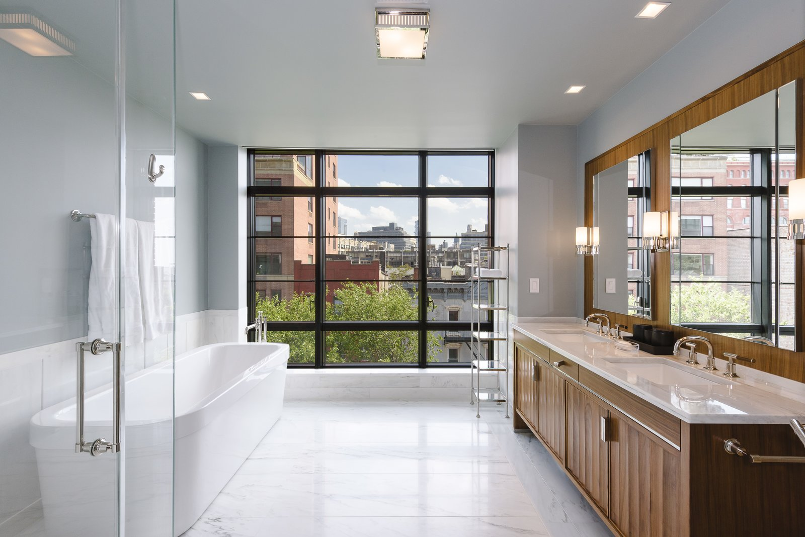 Bath Room, Marble Counter, Ceiling Lighting, Drop In Sink, Enclosed Shower, Freestanding Tub, and Travertine Floor The luxurious master bath has a double vanity, soaking tub, glass enclosed stall shower and wall of windows.  Best Photos from Jon Bon Jovi Sells His West Village Duplex For $16M
