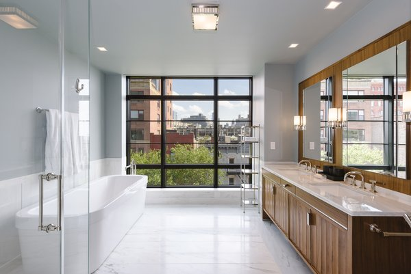 The luxurious master bath has a double vanity, soaking tub, glass enclosed stall shower and wall of windows.