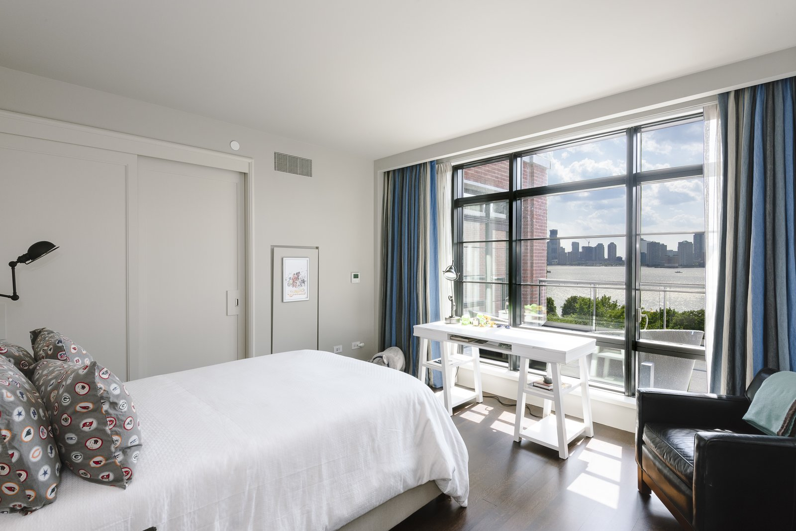 Bedroom, Chair, Bed, and Medium Hardwood Floor There are three bedrooms with en-suite bathrooms and the master's suite features a walk-in closet.  Photo 7 of 8 in Jon Bon Jovi Sells His West Village Duplex For $16M