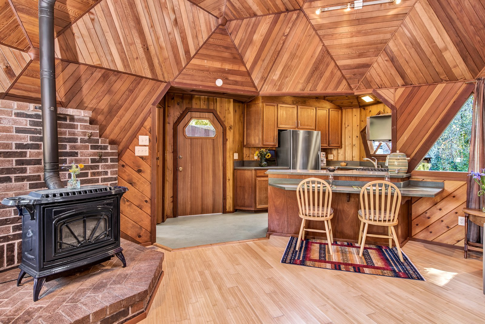 Dining Room, Track Lighting, Chair, Wood Burning Fireplace, Light Hardwood Floor, Rug Floor, Stools, Bar, and Ceiling Lighting The wood-burning stove keeps the home warm on cool nights.  Best Photos from A Geodesic Getaway in Northern California Asks $475K