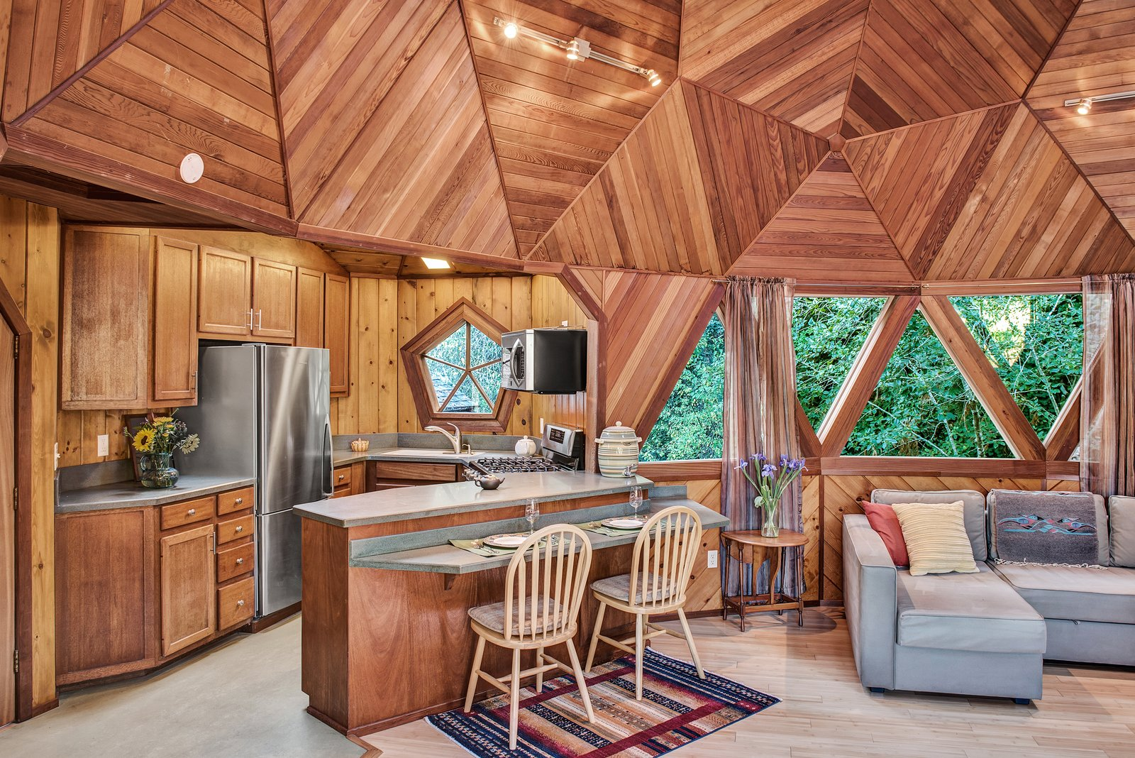 Kitchen, Laminate, Wood, Refrigerator, Light Hardwood, Microwave, Wood, Concrete, Ceiling, Range, Track, and Drop In Triangular windows let plenty of light in.  Best Kitchen Wood Track Ceiling Concrete Refrigerator Light Hardwood Drop In Photos from A Geodesic Getaway in Northern California Asks $475K