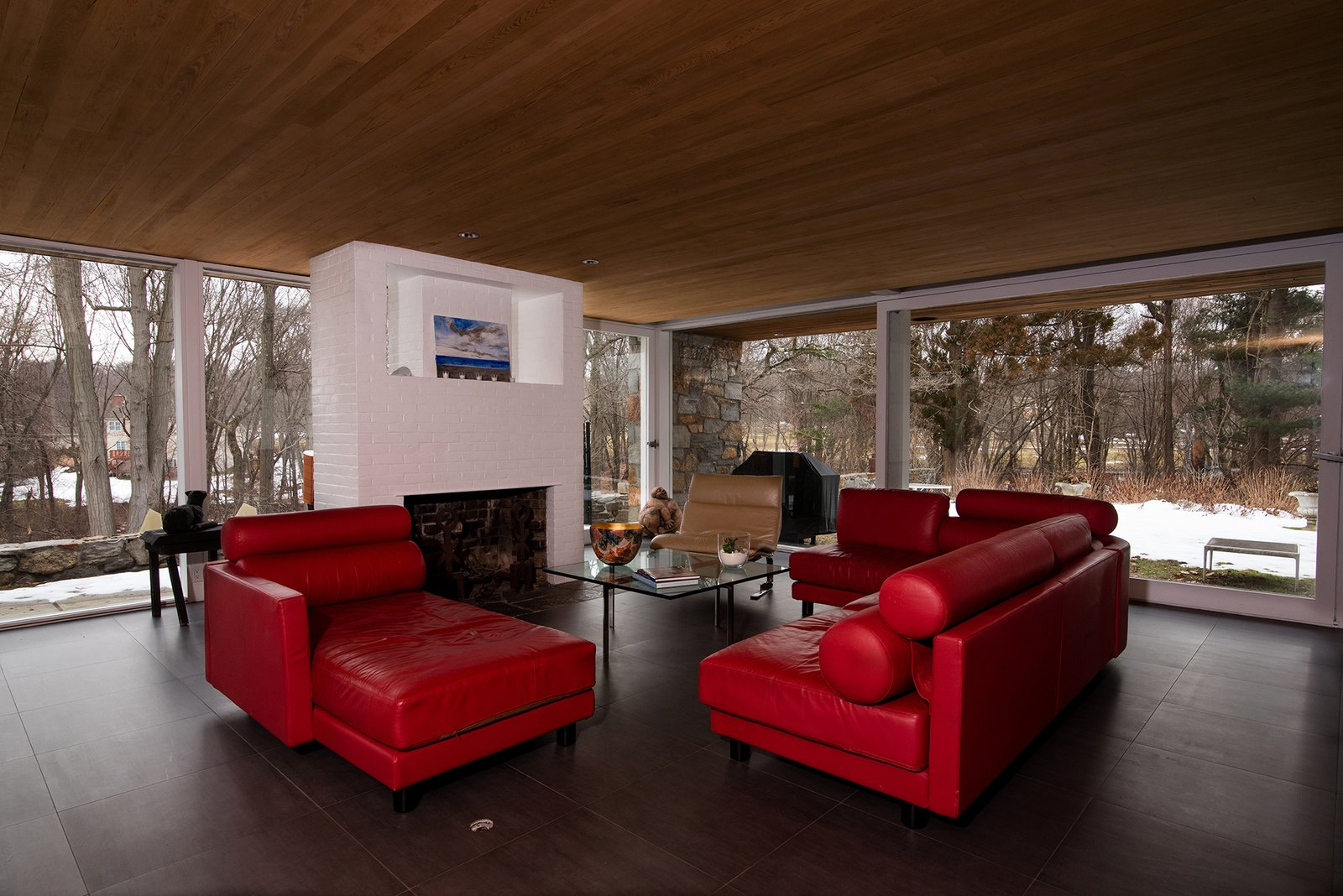 Living Room, Wood Burning Fireplace, Slate Floor, Sofa, End Tables, Recessed Lighting, Coffee Tables, and Chair Every room enjoys expansive views of the surrounding nature.  Photo 4 of 13 in Snag This Midcentury Gem by Marcel Breuer That's Listed For $999K