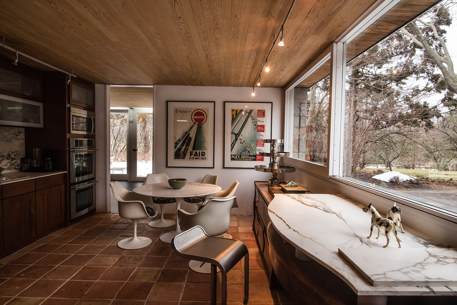 Kitchen, Wood Cabinet, Wall Oven, Ceramic Tile Floor, Track Lighting, and Microwave The kitchen has been updated.  Photo 8 of 13 in Snag This Midcentury Gem by Marcel Breuer That's Listed For $999K