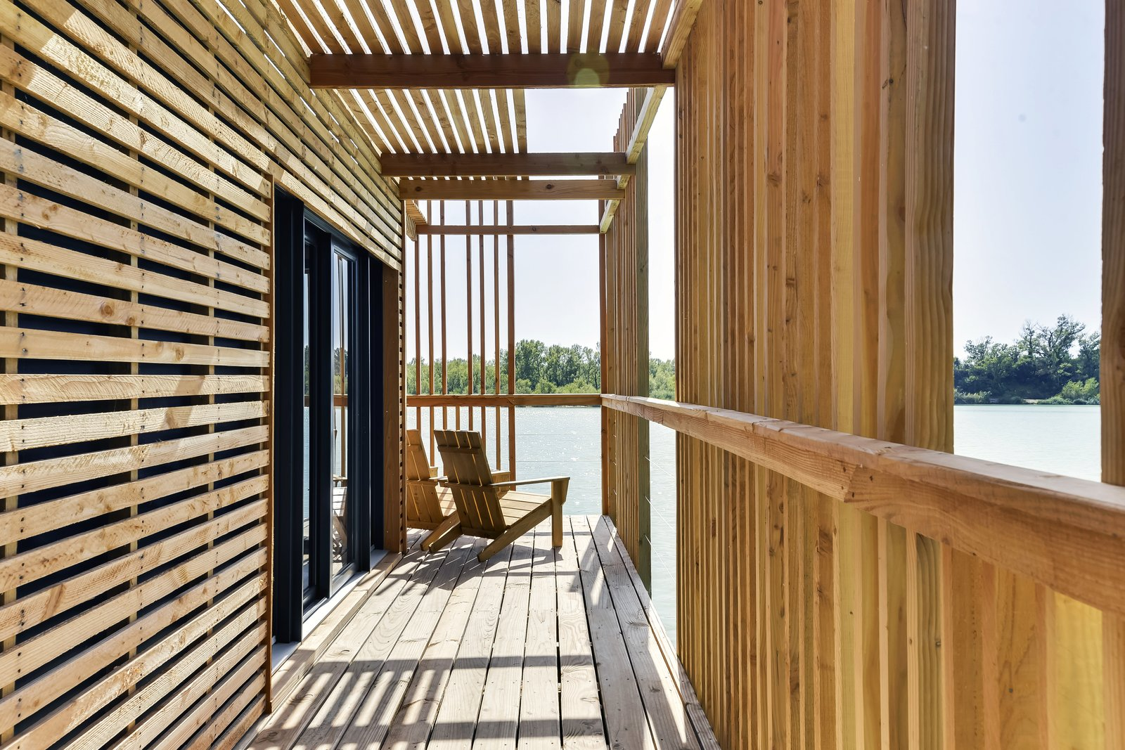 Outdoor and Wood Patio, Porch, Deck During the day, the experience inside the suite is a play of light and shadow with the sun filtering through the screening, projecting motifs always moving on the floor.  Photo 6 of 13 in Drift Off in a Prefab Cabin at This Floating Hotel in France