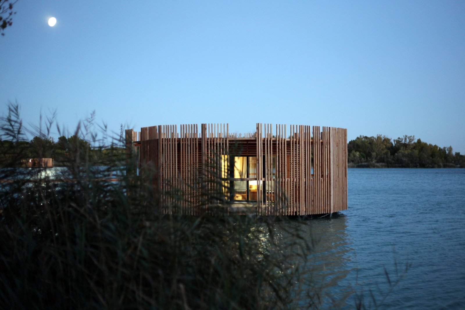 Exterior, Prefab Building Type, Flat RoofLine, Wood Siding Material, and Cabin Building Type After sunset the effect is reversed, and a radiating internal glow emerges from between the wooden slats.  Photo 11 of 13 in Drift Off in a Prefab Cabin at This Floating Hotel in France