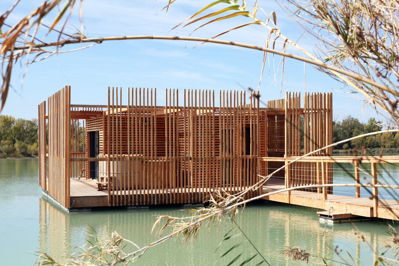 Exterior, Prefab Building Type, Flat RoofLine, Wood Siding Material, and Cabin Building Type A view of the surrounding wraparound deck and wooden privacy screens.  Photo 4 of 13 in Drift Off in a Prefab Cabin at This Floating Hotel in France