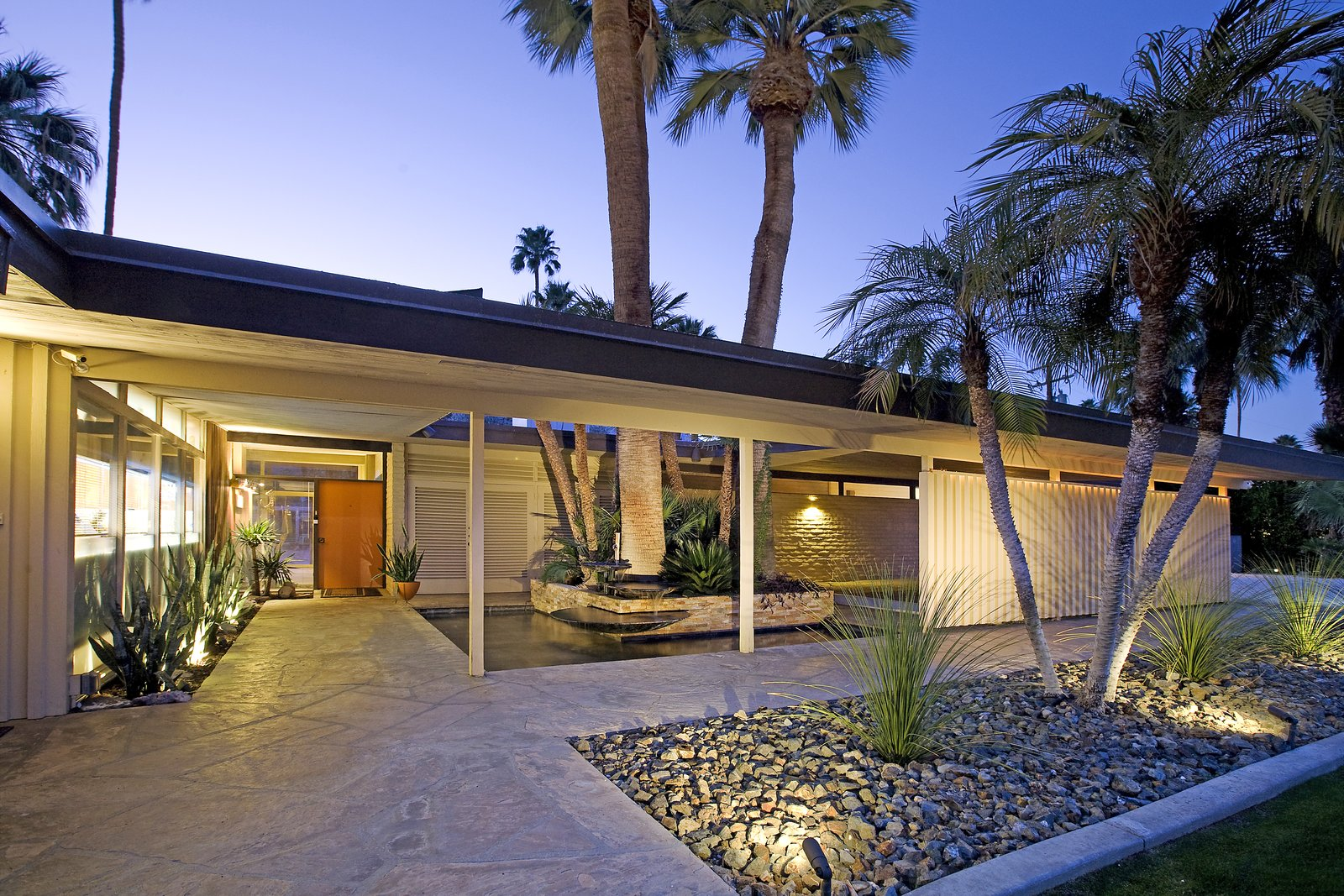 Outdoor, Walkways, Shrubs, Trees, Garden, Side Yard, Wood, Desert, Gardens, and Horizontal A fountain that spills into a palm sheltered pond at the entry.  Outdoor Garden Desert Side Yard Photos from A Luminous Palm Springs Midcentury Asks $3.35M