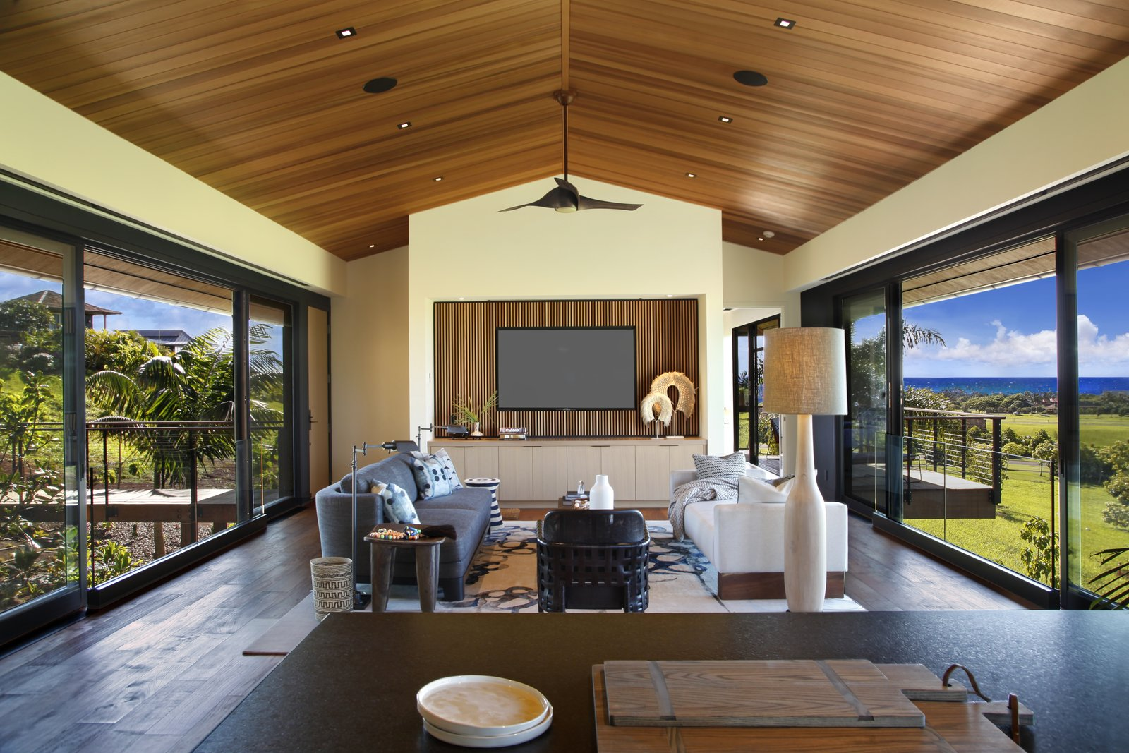 Living Room, Ceiling Lighting, Coffee Tables, Dark Hardwood Floor, and Sofa Two walls of windows make for stunning vistas.  Photo 2 of 14 in A Breezy Hawaiian Residence by Olson Kundig Hits the Market at $6.95M