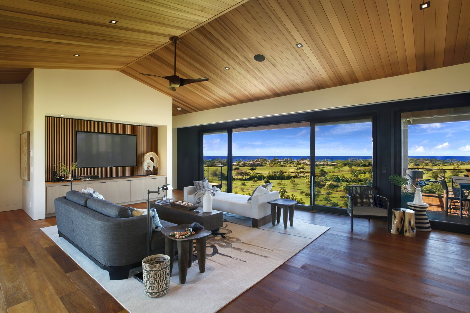 Living Room, Dark Hardwood Floor, End Tables, Coffee Tables, Chair, Sofa, and Ceiling Lighting High ceilings with ceiling fans make for breezy interior.  Photo 3 of 14 in A Breezy Hawaiian Residence by Olson Kundig Hits the Market at $6.95M