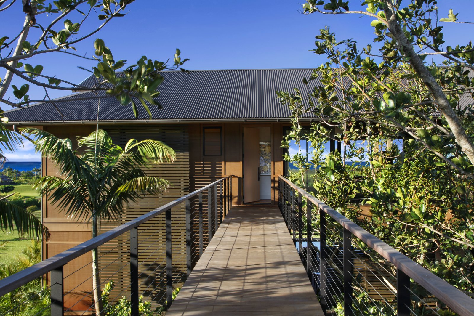 Exterior, Beach House Building Type, Gable RoofLine, Metal Roof Material, and Wood Siding Material The resort-like residence has midcentury modern influences, with a strong tropical vibe.  Photo 1 of 14 in A Breezy Hawaiian Residence by Olson Kundig Hits the Market at $6.95M