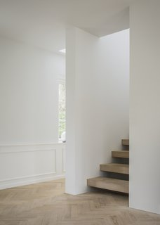 A central staircase creates a dynamic, semi-open space, with floating steps in solid oak, creating a flow that connects the house vertically in a harmonious and contemporary manner.