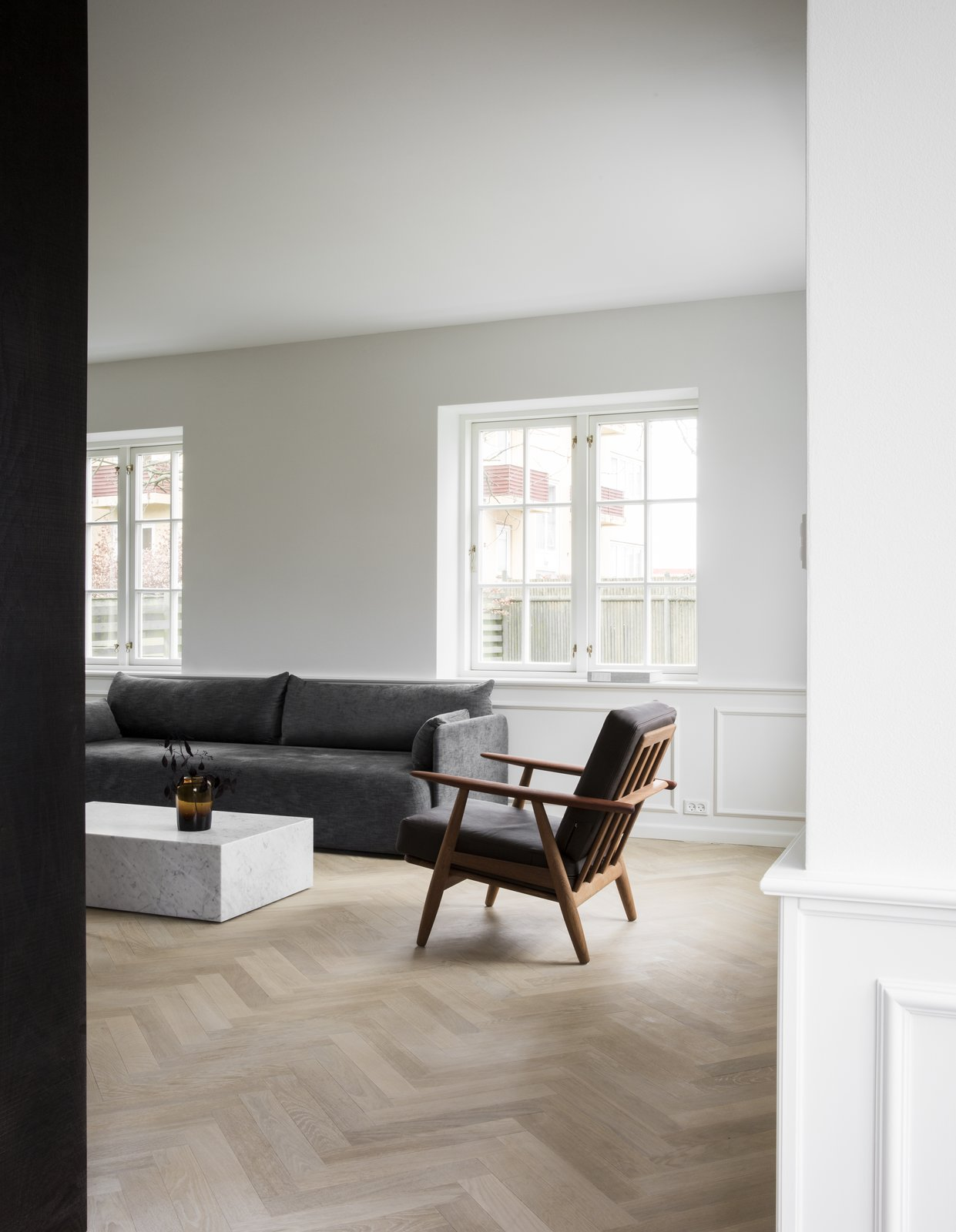 Living Room, Chair, Light Hardwood Floor, Sofa, and Coffee Tables Dark mid-century teak furniture and marble pieces, set against a white background.  Photo 6 of 13 in The Historic Villa Once Home to Poul Henningsen Receives a Modern Renovation