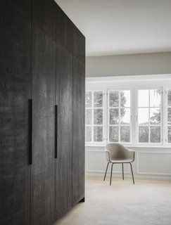 A large kitchen cabinet covered in dark stained oak separates the kitchen from the living room.