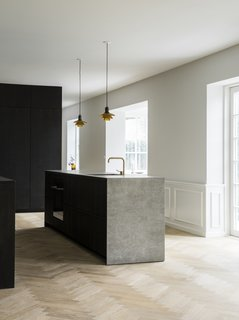 The minimalist kitchen in smoked oak with bronzed brass handles was designed by Norm Architects for the Danish kitchen manufacturer Reform, and is complemented by a sculptural kitchen island in a light gray ceramic stone, as well as a herringbone floor.