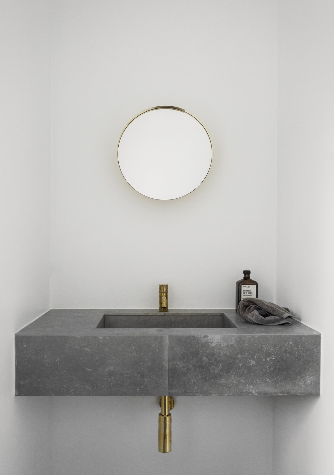 Bath, Stone, Wall Mount, and Undermount Both the kitchen and bathroom of the house feature slim brass faucets.  Bath Undermount Stone Photos from The Historic Villa Once Home to Poul Henningsen Receives a Modern Renovation