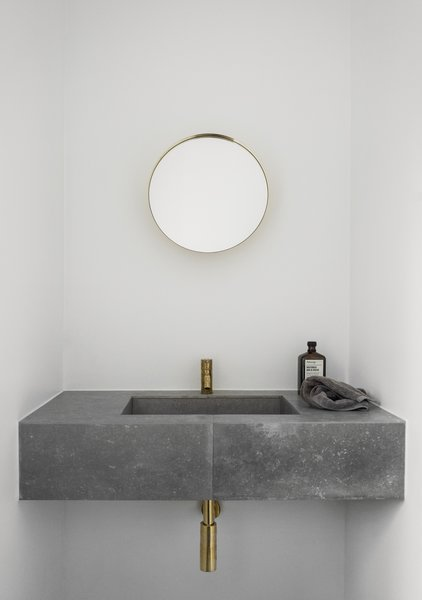 Both the kitchen and bathroom of the house feature slim brass faucets.