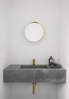 Both the kitchen and bathroom of the redesigned dwelling feature slim brass faucets.