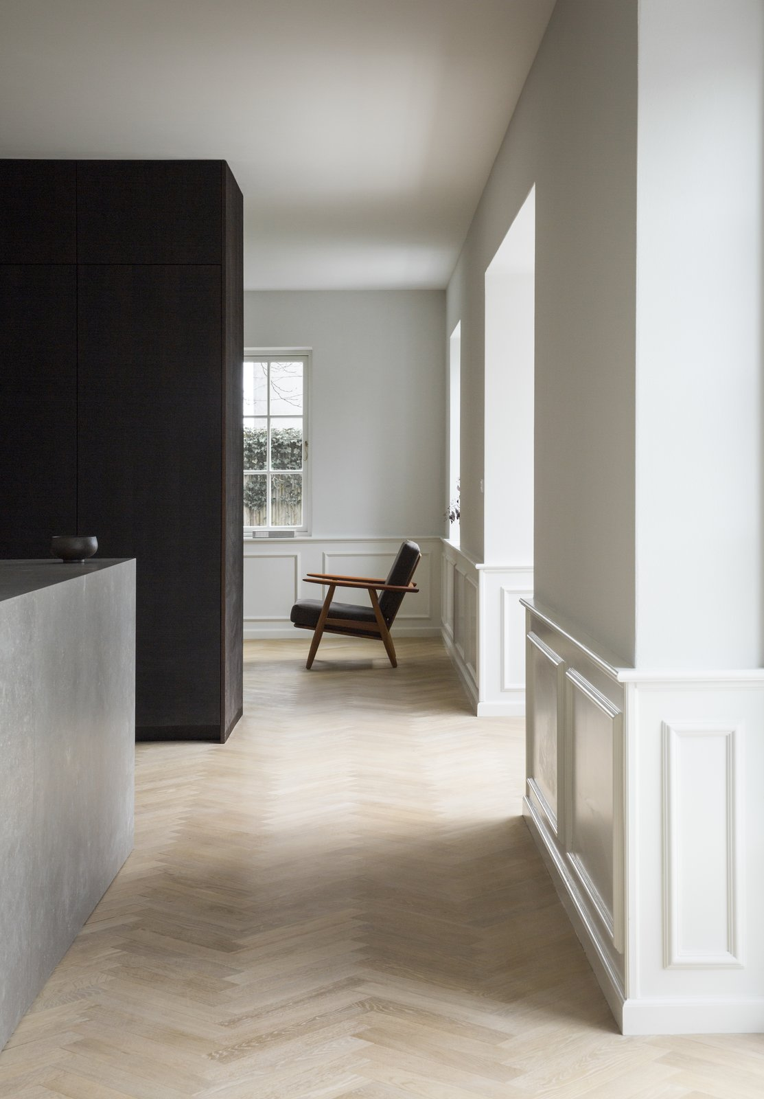 Living Room, Chair, and Light Hardwood Floor With natural lighting entering from every angle, each room of the house is bright, and the interiors feature an elegant play of light and dark.  Photo 4 of 13 in The Historic Villa Once Home to Poul Henningsen Receives a Modern Renovation
