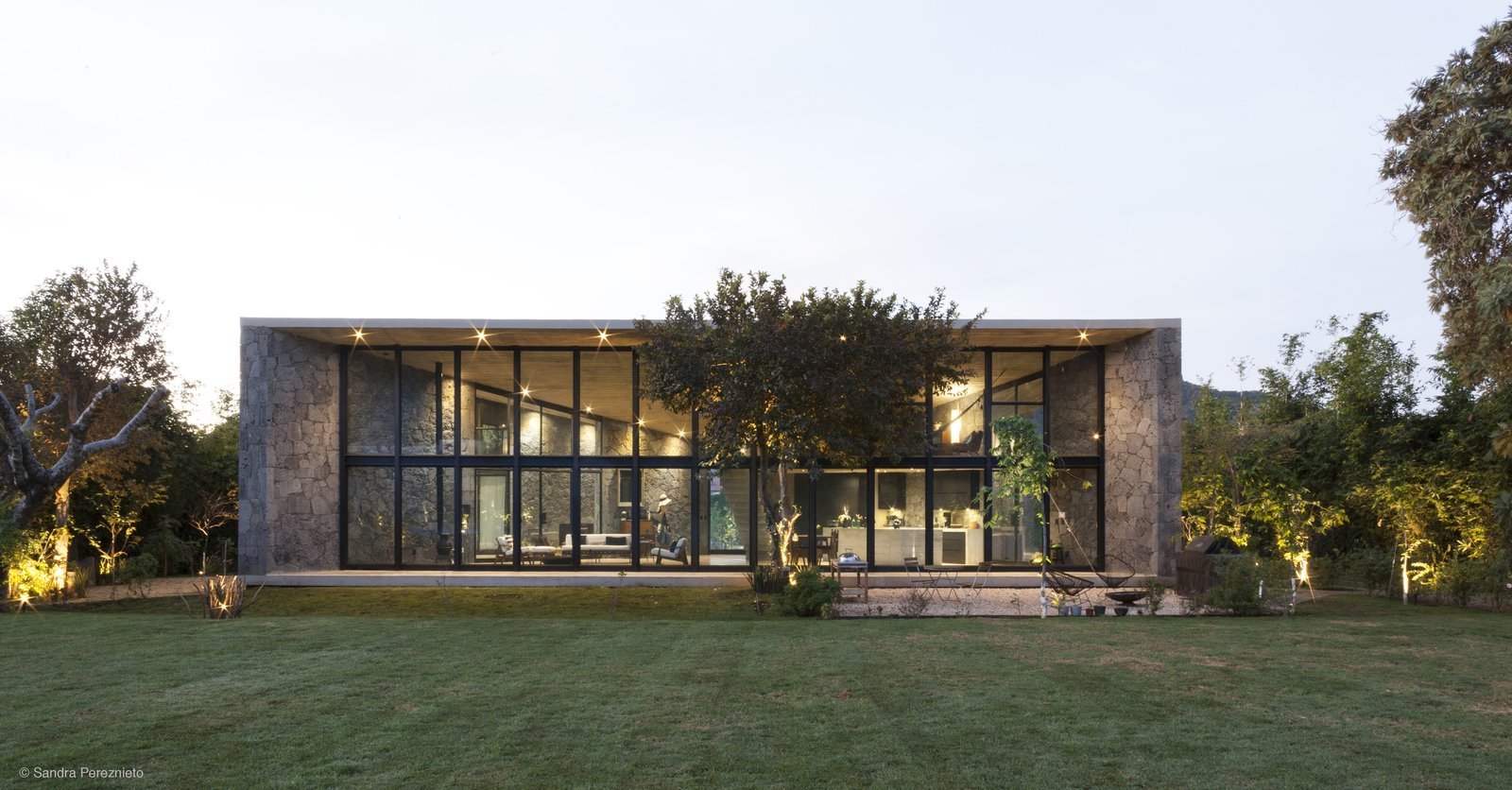 Exterior, House Building Type, Flat RoofLine, Stone Siding Material, and Glass Siding Material The roof is continuous and rests on top of the structural stone walls.  Photo 9 of 10 in A Commanding Mexican Home of Stone and Concrete Is For Sale