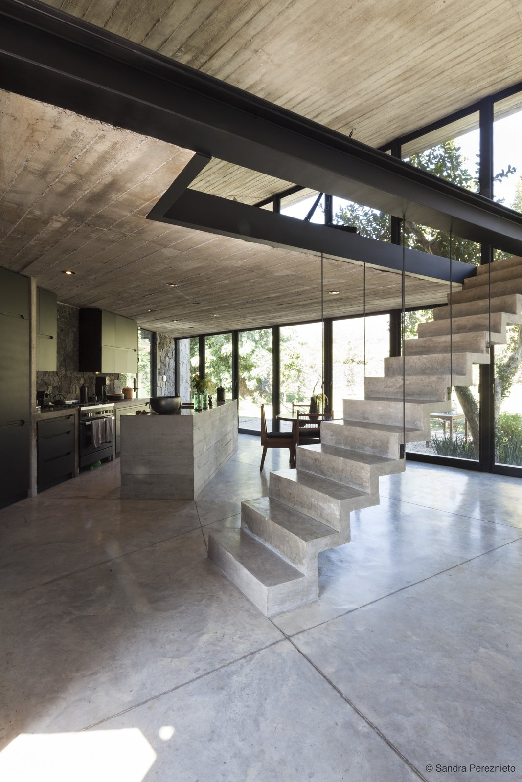 Staircase and Concrete Tread The main living area features a full glass frontage facing the mountains and stairs lead  Photo 3 of 10 in A Commanding Mexican Home of Stone and Concrete Is For Sale
