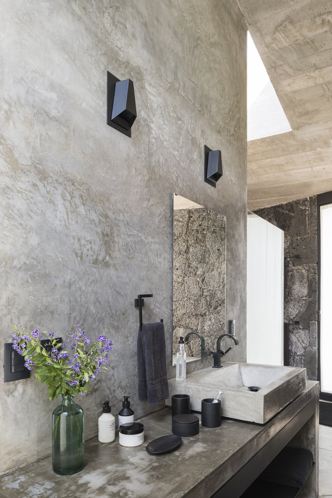 Bath Room, Vessel Sink, Concrete Floor, Concrete Counter, Wall Lighting, and Concrete Wall One of the bathrooms.  Photo 6 of 10 in A Commanding Mexican Home of Stone and Concrete Is For Sale