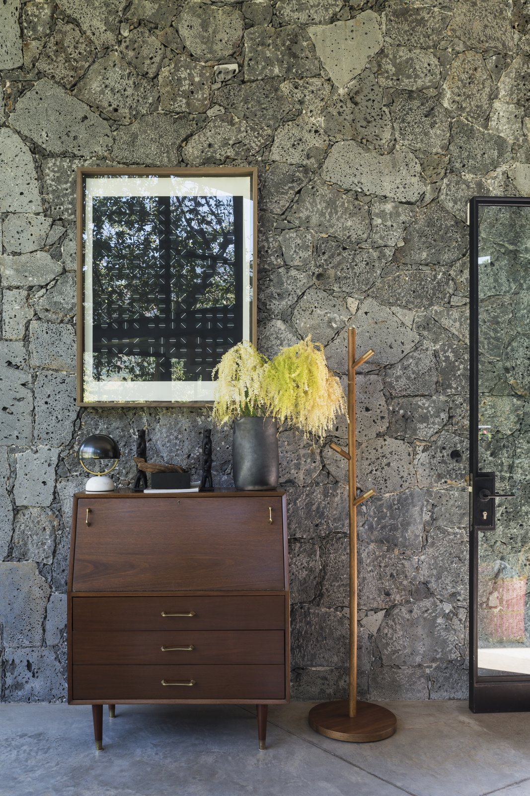 Living Room, Concrete Floor, and Console Tables All of the stone was sourced locally.  Photo 2 of 10 in A Commanding Mexican Home of Stone and Concrete Is For Sale