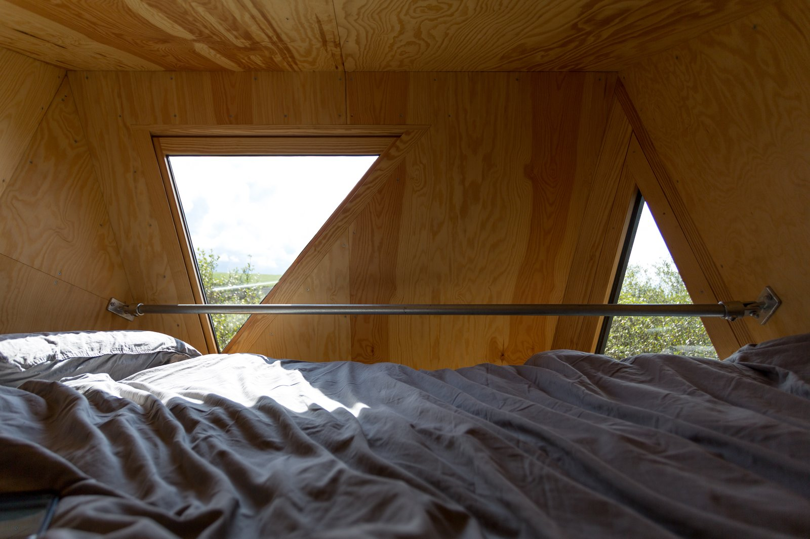 Bedroom and Bed Small triangular windows allow for views of the Cornish countryside.  Photo 8 of 12 in Go Off The Grid With These Remote Rental Cabins in Cornwall
